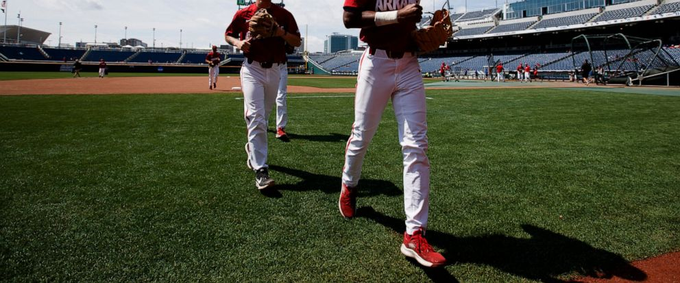 Arkansas Curtis Washington, Jr., right, and Casey Martin head to the dugout during practice for baseballs College World Series at TD Ameritrade Park, Friday, June 14, 2019, in Omaha, Neb. (Ryan Soderlin/Omaha World-Herald via AP)