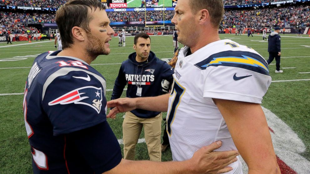 FILE - In this Oct. 29, 2017, file photo, New England Patriots quarterback Tom Brady (12) and Los Angeles Chargers quarterback Philip Rivers (17) speak at midfield after an NFL football game, in Foxborough, Mass. The Chargers and Patriots meet in a divisional playoff game on Sunday, Jan. 13, 2019. (AP Photo/Steven Senne, File)