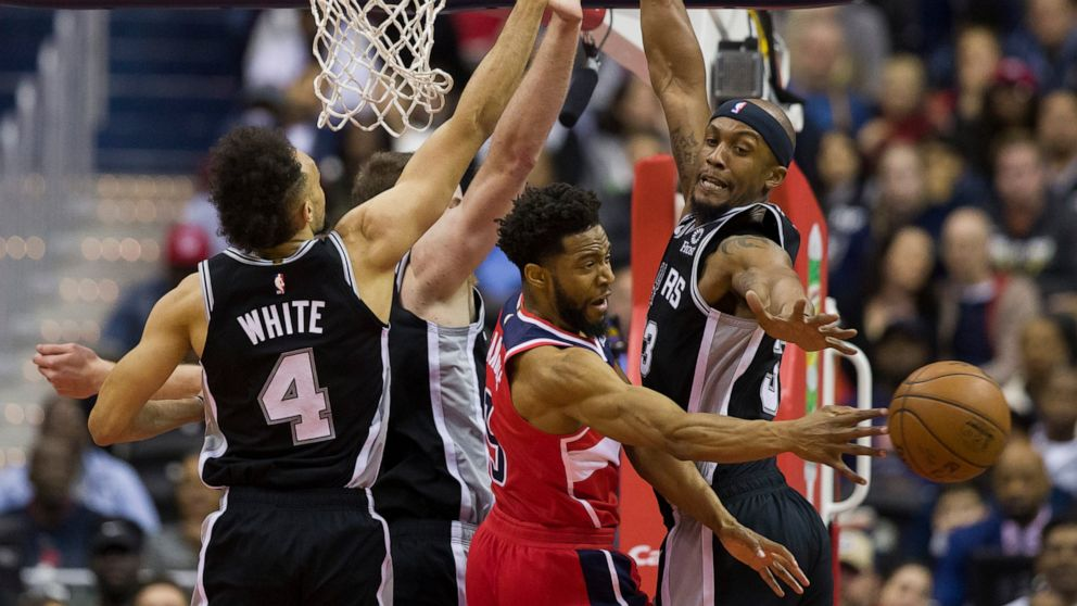 Washington Wizards guard Chasson Randle passes the ball between San Antonio Spurs guard Derrick White, left, center Jakob Poeltl, from Austria, and forward Dante Cunningham, right, during the first half of an NBA basketball game Friday, April 5, 2019, in Washington. (AP Photo/Alex Brandon)