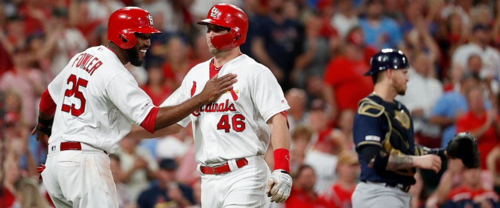 St. Louis Cardinals Paul Goldschmidt (46) is congratulated by teammate Dexter Fowler (25) after hitting a three-run home run as Milwaukee Brewers catcher Yasmani Grandal, right, stands at the plate during the sixth inning of a baseball game Friday,