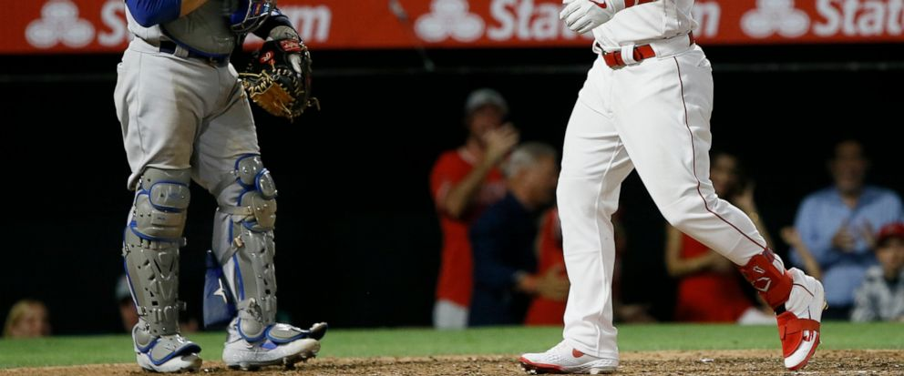 Los Angeles Angels Mike Trout, right, points after hitting a two-run home run with Los Angeles Dodgers catcher Russell Martin watching during the seventh inning of a baseball game against the Los Angeles Dodgers in Anaheim, Calif., Monday, June 10,