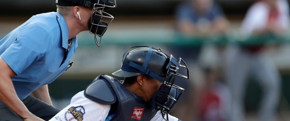 Home plate umpire Brian deBrauwere, left, huddles behind Freedom Division catcher James Skelton, of the York Revolution, as the official wears an earpiece during the first inning of the Atlantic League All-Star minor league baseball game, Wednesday,