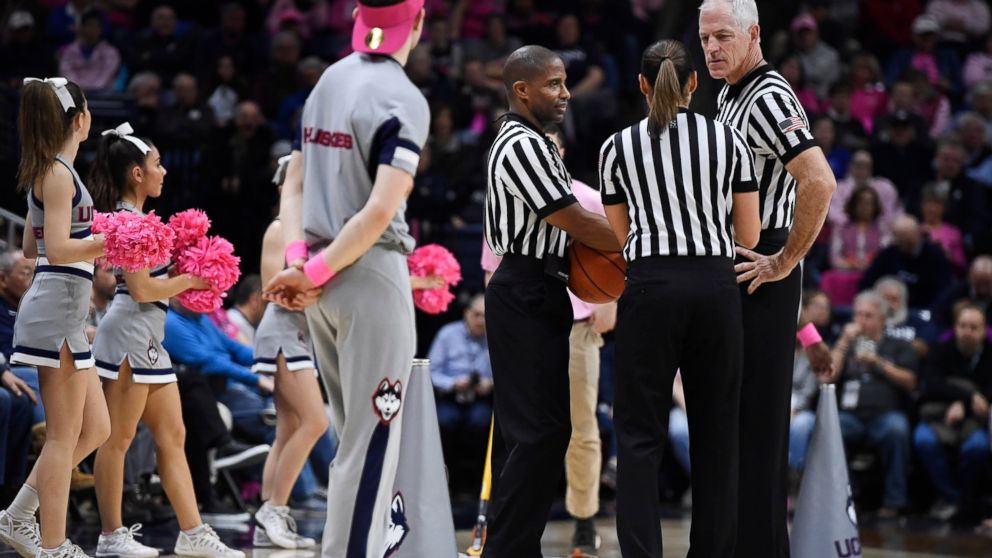 Referee Bruce Morris, right, officiates an NCAA college basketball game between Connecticut and Temple with Eric Brewton, left, and Tiara Cruse, center,, Saturday, Feb. 9, 2019, in Storrs, Conn. Morris holds an NCAA record for the longest shot recorded.(AP Photo/Jessica Hill)