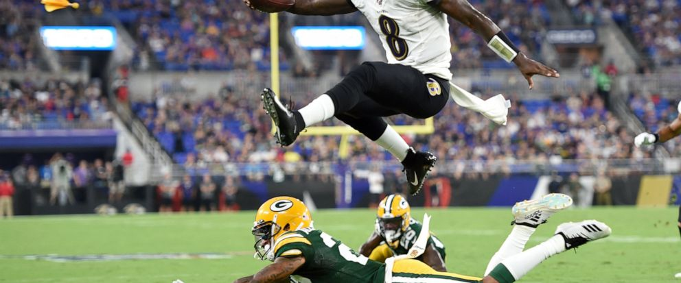 Baltimore Ravens quarterback Lamar Jackson (8) leaps over Green Bay Packers cornerback Jaire Alexander (23) during the first half of a NFL football preseason game, Thursday, Aug. 15, 2019, in Baltimore. The play was called back on a penalty on the Ra