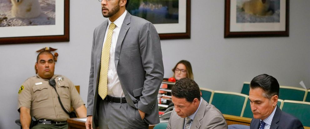 Ex-NFL player Kellen Winslow II, standing, who was accused of committing several sex crimes against women in North County last year, including rape, answers a question from San Diego County Superior Court Vista Judge Blaine Bowman during a status hea