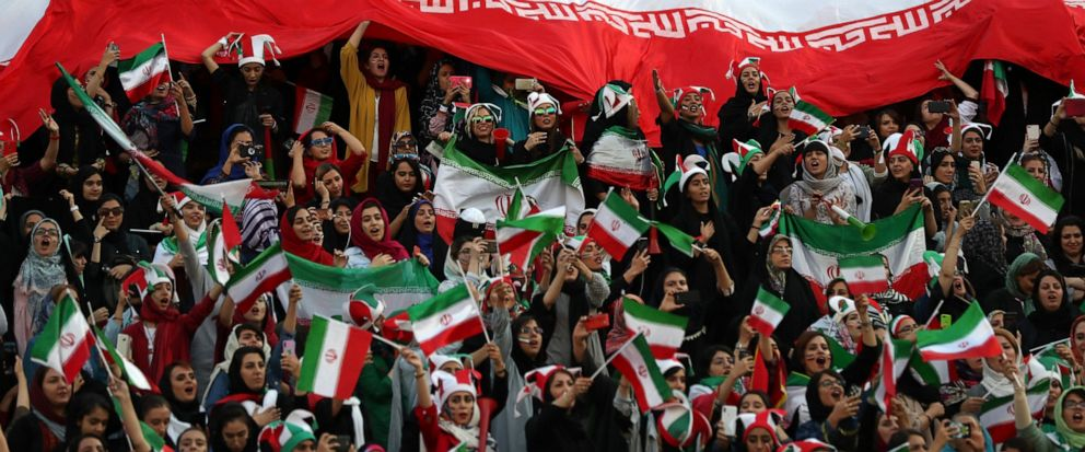 Iranian women cheer as they hold a huge Iranian flag during a soccer match between their national team and Cambodia in the 2022 World Cup qualifier at the Azadi (Freedom) Stadium in Tehran, Iran, Thursday, Oct. 10, 2019. Iranian women were freely all