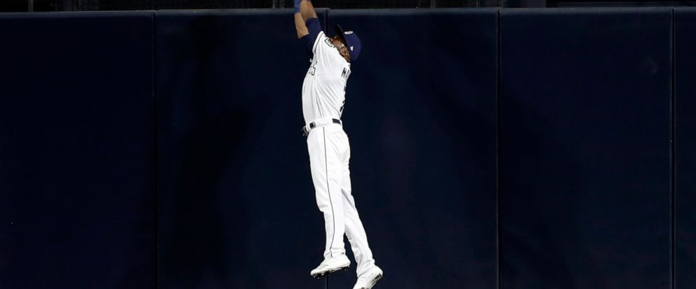 San Diego Padres center fielder Manuel Margot makes the catch above the wall for the out on Chicago Cubs Nicholas Castellanos during the fourth inning of a baseball game Wednesday, Sept. 11, 2019, in San Diego. (AP Photo/Gregory Bull)