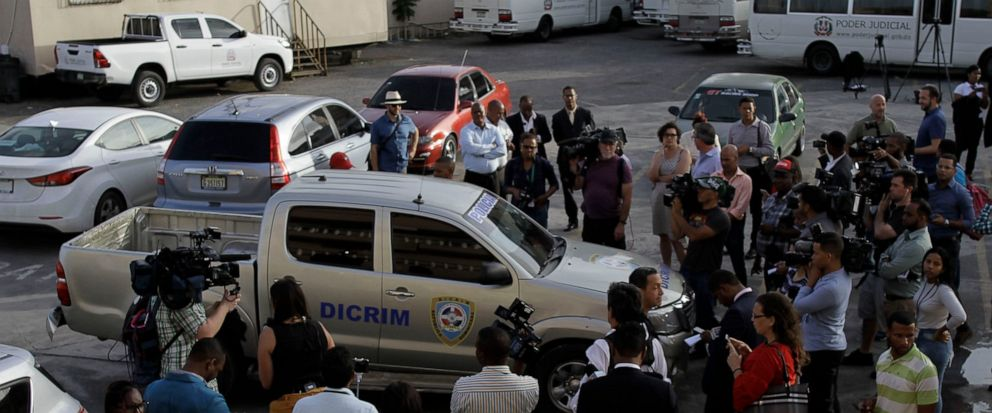 Journalists surround the police vehicle carrying Eddy Vladimir Féliz Garcia who was taken into custody in connection with the shooting of former Boston Red Sox slugger David Ortiz, as he is taken to court in Santo Domingo, Dominican Republic, Tuesday