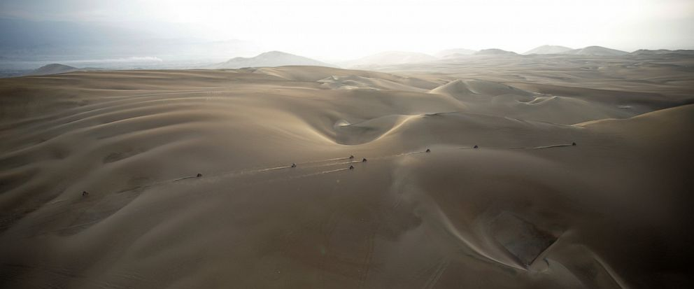 """FILE - In this Jan. 16, 2019 photo, competitors ride their motorbikes across the dunes during stage nine of the Dakar Rally in Pisco, Peru. Dakar organizers say next years cross-country race will be held in """"the deep and mysterious deserts of the Mi"""