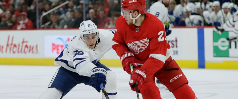 Toronto Maple Leafs right wing Ilya Mikheyev (65), of Russia, tries to steal the puck from Detroit Red Wings defenseman Dennis Cholowski (21), of the Czech Republic, during the first period of an NHL hockey game, Saturday, Oct. 12, 2019, in Detroit.