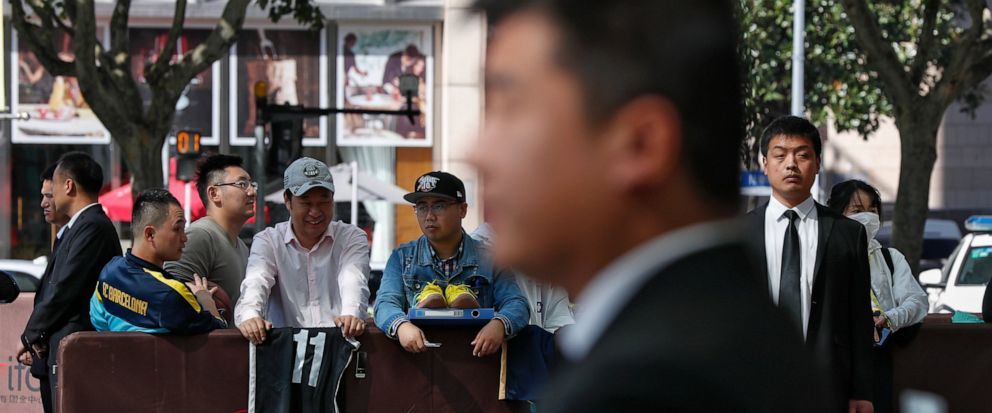 Chinese security officers stand guard as fans carrying jerseys and shoes wait for NBA players to autograph outside the Ritz-Carlton hotel in Shanghai, China, Thursday, Oct. 10, 2019. NBA Commissioner Adam Silver told the Brooklyn Nets and Los Angeles