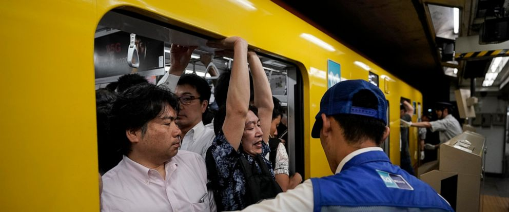 In this July 30, 2019, photo, a station attendant watches as a commuter struggles to squeeze himself into an overcrowded train during morning rush hours at Akasaka Mitsuke Station in Tokyo. Tokyo has one of the most advanced public transport systems