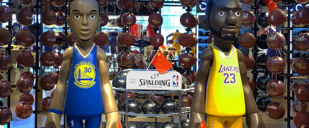 Statues of NBA players Stephen Curry of the Golden State Warriors, left, and Lebron James of the Los Angeles Lakers hold Chinese flags in the entrance of an NBA merchandise store in Beijing, Tuesday, Oct. 8, 2019. Chinese state broadcaster CCTV annou