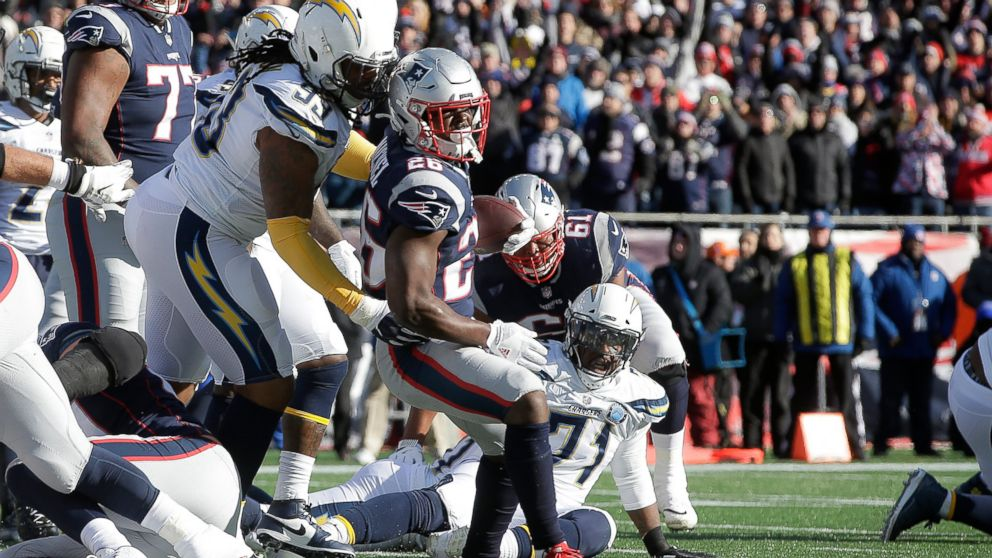 New England Patriots running back Sony Michel (26) scores a touchdown in front of Los Angeles Chargers defensive tackle Darius Philon (93) during the first half of an NFL divisional playoff football game, Sunday, Jan. 13, 2019, in Foxborough, Mass. (AP Photo/Steven Senne)