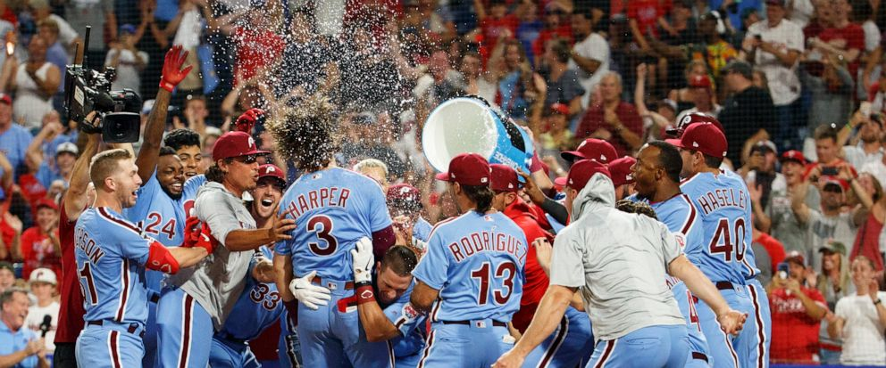 Philadelphia Phillies Bryce Harper (3) celebrates his grand slam with teammates during the ninth inning of a baseball game against the Chicago Cubs, Thursday, Aug. 15, 2019, in Philadelphia. The Phillies won 7-5. (AP Photo/Chris Szagola)
