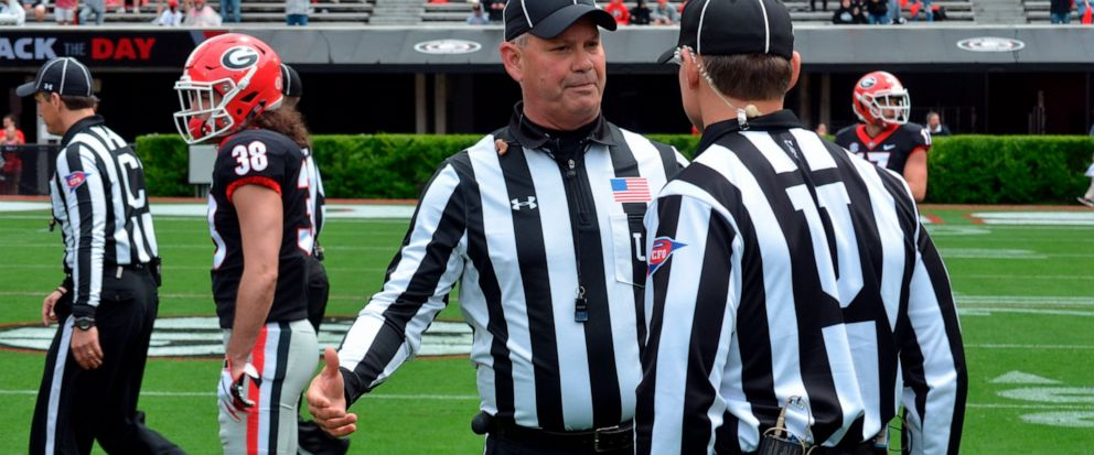 In this April 20, 2019 photo, Tom Quick talks with a colleague during Georgias spring NCAA college football game in Athens, Ga. They're jobs have never been more difficult. Those who do it face relentless, often uninformed criticism, and attacks on