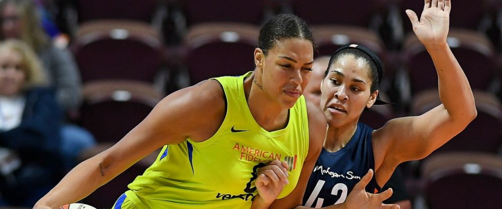 FILE - In this May 8, 2018, file photo, Dallas Wings Liz Cambage, left, drives against Connecticut Suns Brionna Jones during a preseason WNBA basketball game in Uncasville, Conn. A person familiar with the situation tells The Associated Press that