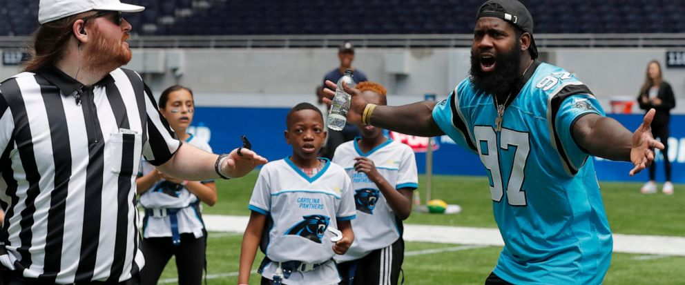 NFL player Mario Addison of the Carolina Panthers complains to the referee as he coaches a young team during the final tournament for the UKs NFL Flag Championship, featuring qualifying teams from around the country, at the Tottenham Hotspur Stadium