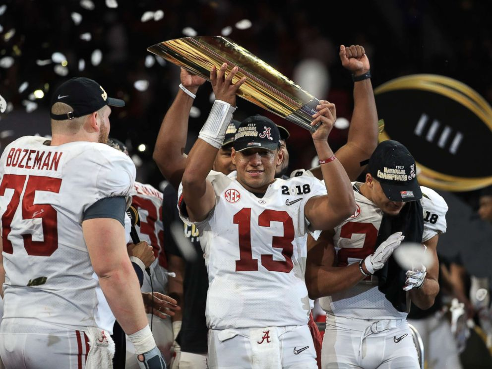 PHOTO: Tua Tagovailoa of the Alabama Crimson Tide holds the trophy while celebrating with his team after defeating the Georgia Bulldogs in overtime to win the CFP National Championship presented by AT&T at Mercedes-Benz Stadium, Jan. 8, 2018, in Atlanta.