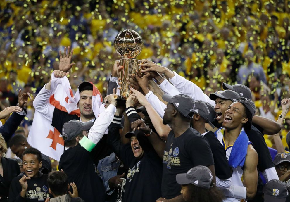 PHOTO: Golden State Warriors players, coaches and owners hold up the Larry OBrien NBA Championship Trophy after Game 5 of basketballs NBA Finals between the Warriors and the Cleveland Cavaliers in Oakland, Calif., June 12, 2017.
