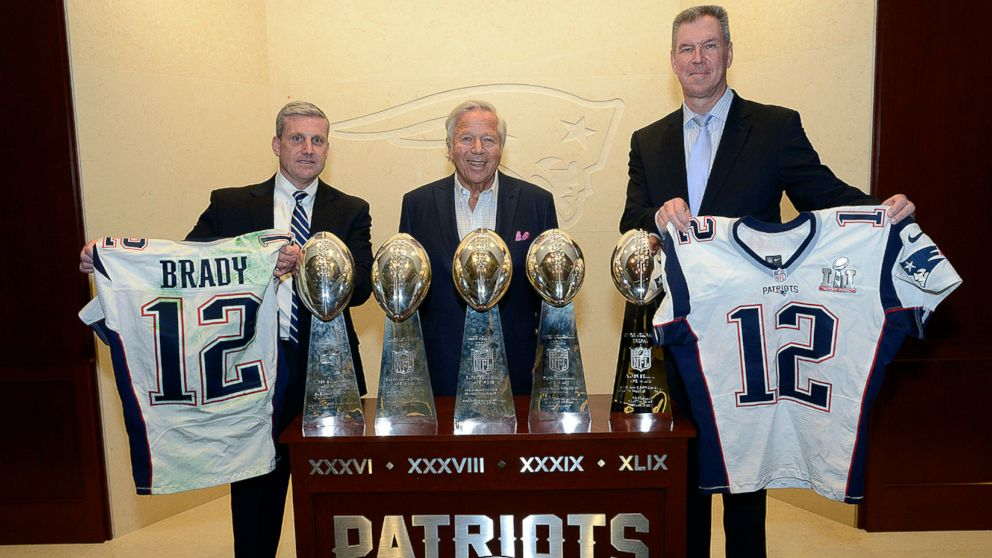 Harold H. Shaw, left, Special Agent in Charge of the FBI Boston Division and Colonel Richard D. McKeon, right, of the Massachusetts State Police, hold two recovered Super Bowl jerseys worn by Tom Brady, beside team owner Robert Kraft, center, March 23, 2017, in the NFL football team's trophy room at Gillette Stadium in Foxborough, Mass.
