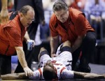 PHOTO:Trainers check on Louisville guard Kevin Ware (5) after Ware injured his lower right leg during the first half of the Midwest Regional final against Duke in the NCAA college basketball tournament, Sunday, March 31, 2013, in Indianapolis.