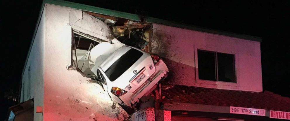 PHOTO: A vehicle that crashed into a building hangs from a second story window in Santa Ana, Calif., Kam/ 14. 2018. Two people escaped serious injuries when the car hit a divider, went airborne and slammed into the second floor of a dental office.