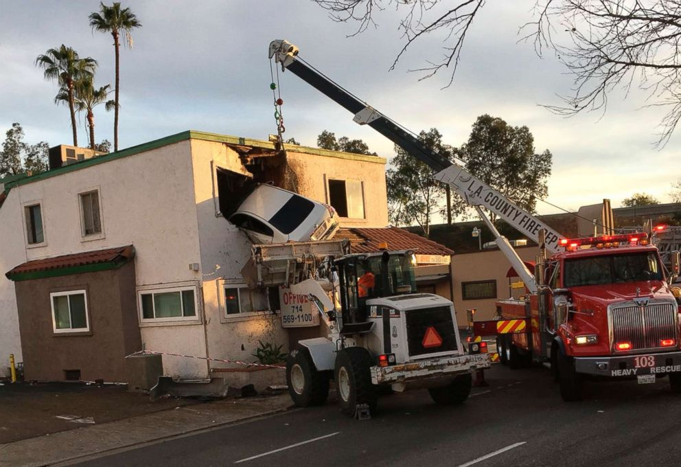 PHOTO: A crane is used to remove a vehicle hanging from a second story window after it hit a center divider and went airborne in Santa Ana, Calif., Jan. 14, 2018.