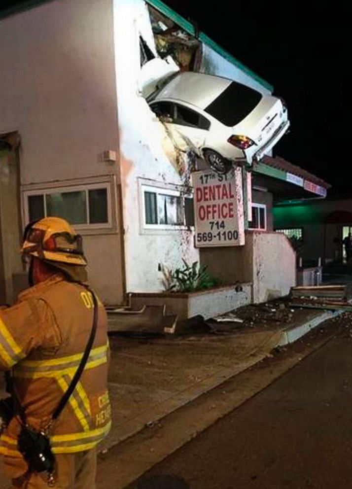 PHOTO: A vehicle that crashed into a building hangs from a second story window in Santa Ana, Calif., Jan. 14, 2018. Two people in the car escaped serious injuries after the car went airborne and slammed into the second floor of a dental office.