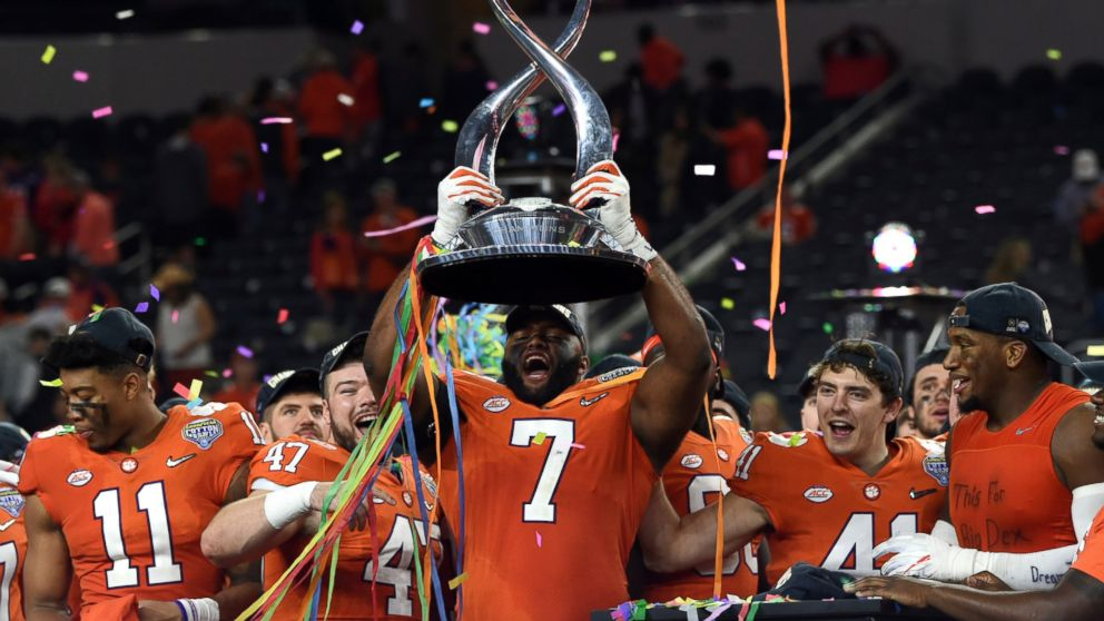 Clemson defensive end Austin Bryant (7) holds up the trophy as the team celebrates their 30-3 win against Notre Dame in the NCAA Cotton Bowl semi-final playoff football game, Saturday, Dec. 29, 2018, in Arlington, Texas.