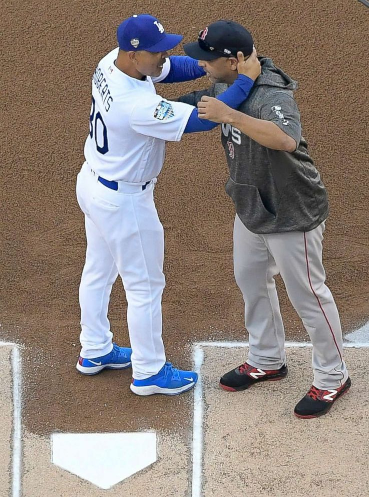 PHOTO: Los Angeles Dodgers manager Dave Roberts and Boston Red Sox manager Alex Cora hug before Game 3 of the World Series baseball game on Friday, Oct. 26, 2018, in Los Angeles.