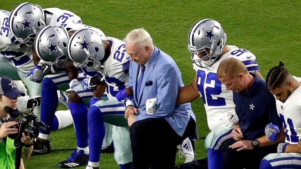 The Dallas Cowboys, led by owner Jerry Jones, center, take a knee prior to the national anthem prior to an NFL football game against the Arizona Cardinals, Sept. 25, 2017, in Glendale, Ariz.