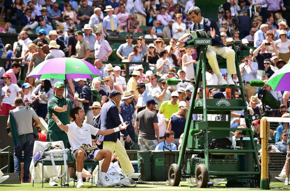PHOTO: Serbias Novak Djokovic receives a court violation from the umpire after throwing his racket while playing Japans Kei Nishikori during their mens singles quarter-finals match on the ninth day of the 2018 Wimbledon Championships, July 11, 2018.