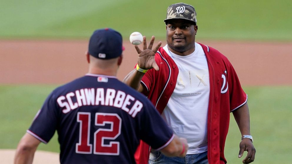 PHOTO: U.S. Capitol Police officer Eugene Goodman catches the ball from Washington Nationals' Kyle Schwarber after throwing out the first pitch before the Washington Nationals baseball game against the New York Mets, Friday, June 18, 2021, in Washington.