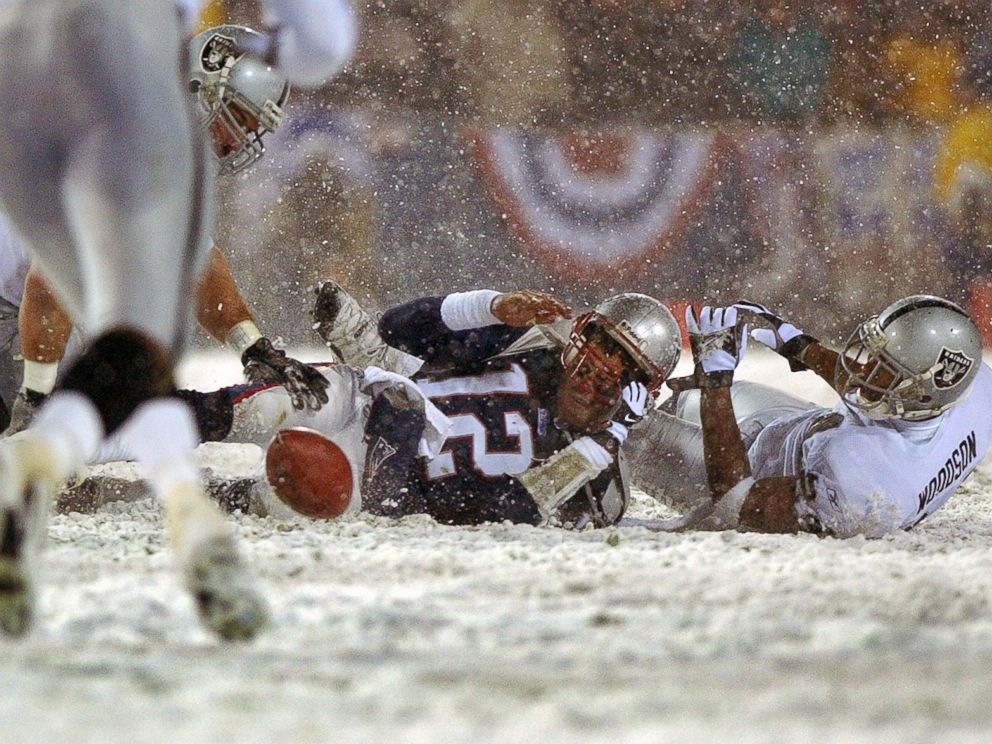 PHOTO: Patriots quarterback Tom Brady loses the ball after being hit by the Oakland Raiders Charles Woodson, right, Jan. 19, 2002.