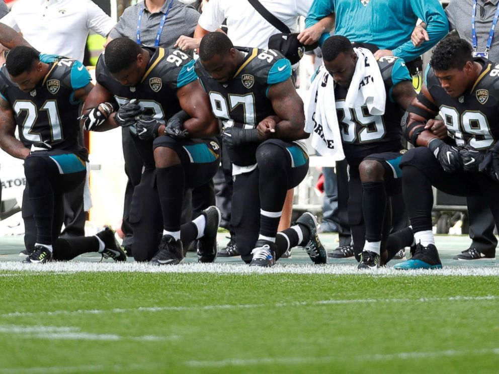 PHOTO: Jacksonville Jaguars players lock arms and kneel down during the playing of the U.S. national anthem before an NFL football game against the Baltimore Ravens at Wembley Stadium in London, Sunday Sept. 24, 2017.