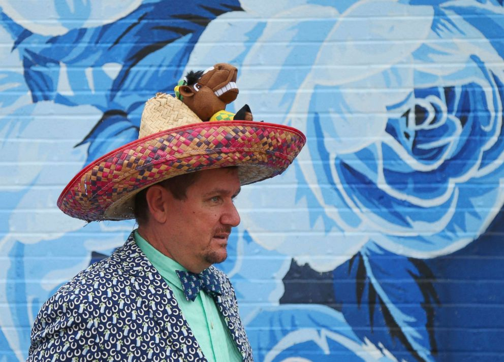 PHOTO: A man walks past a mural in his Cinco de Mayo themed derby hat during the 144th running of the Kentucky Derby at Churchill Downs, May 5, 2018 in Louisville, Ky.