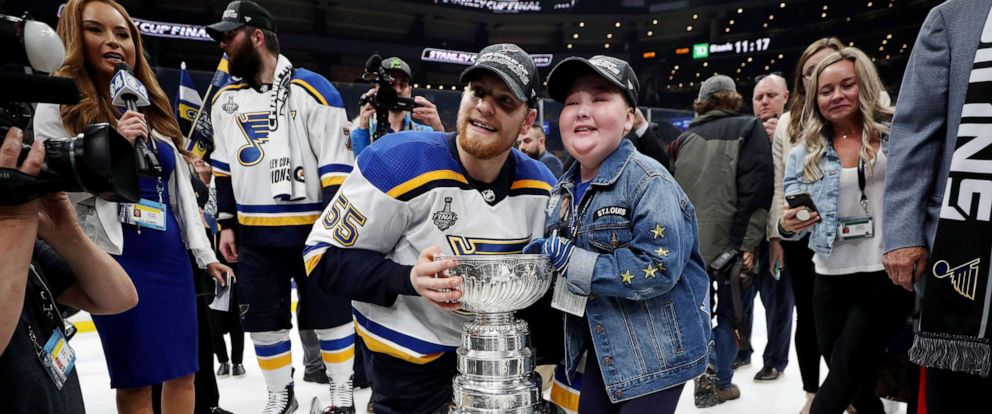 PHOTO: Colton Parayko #55 of the St. Louis Blues and Laila Anderson celebrate with the Stanley Cup after defeating the Boston Bruins in 2019 NHL Stanley Cup Final at TD Garden, June 12, 2019 in Boston.