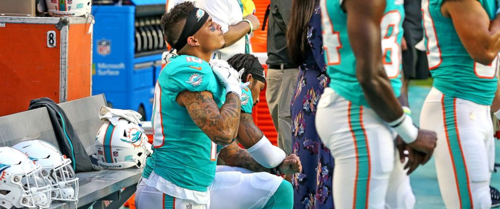 PHOTO: Miami Dolphins receivers Kenny Stills and Albert Wilson kneel during the national anthem as they prepare to play the Tampa Bay Buccaneers at Hard Rock Stadium in Miami Gardens, Fla., Aug. 9, 2018.