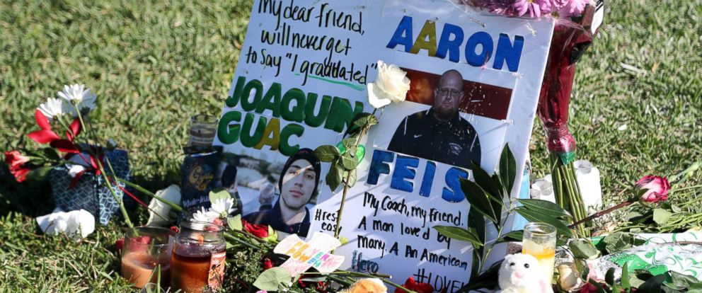 PHOTO: A tribute to student Joaquin Oliver and coach Aaron Feis is left at the base of a white cross at Pine Trails Park in Parkland, Fla., Feb. 16, 2018.