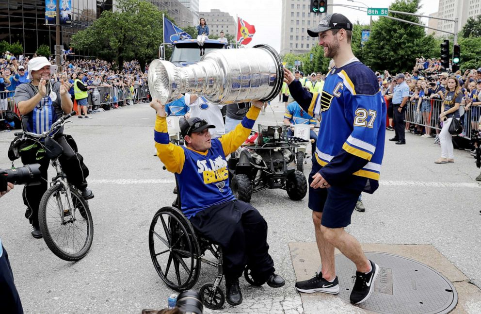 PHOTO: St. Louis Blues defenseman and captain Alex Pietrangelo, right, hands the Stanley Cup to a fan during the Blues NHL hockey Stanley Cup victory celebration in St. Louis.