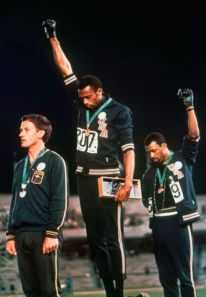 In this Oct. 16, 1968 file photo, extending gloved hands skyward in a Black power salute as a form of racial protest, athletes Tommie Smith, center, and John Carlos stare downward during the playing of the national anthem after Smith received the gold and Carlos the bronze for the 200 meter run at the Summer Olympic Games in Mexico City.