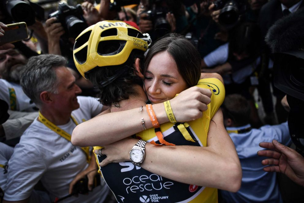 PHOTO: Tour de France winner Geraint Thomas (L) wearing the overall leaders yellow jersey hugs his wife Sarah-Ellen (R) as he celebrates after the 21st and last stage of the 105th edition of the Tour de France cycling race in Paris, July 29, 2018.