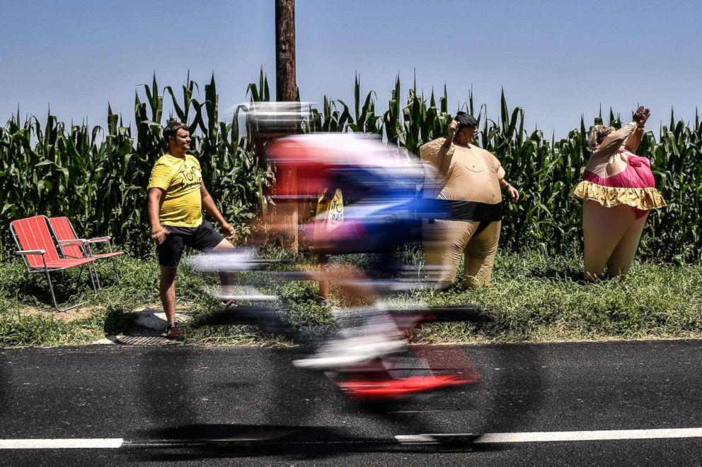 PHOTO: Spectators dressed in inflatable costumes cheer as a rider speeds past during the 18th stage of the 105th edition of the Tour de France cycling race, July 26, 2018 between Trie-sur-Baise and Pau, southwestern France.