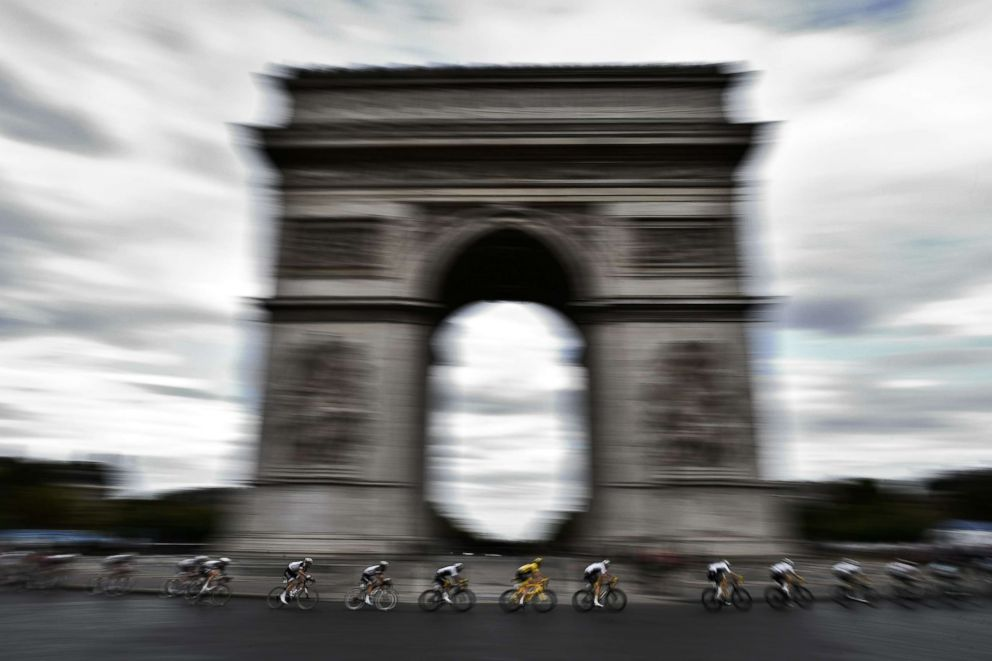 PHOTO: Great Britains Geraint Thomas (C) wearing the overall leaders yellow jersey rides past the Arc de triomphe monument during the Tour de France cycling race between Houilles and Paris Champs-Elysees, July 29, 2018.