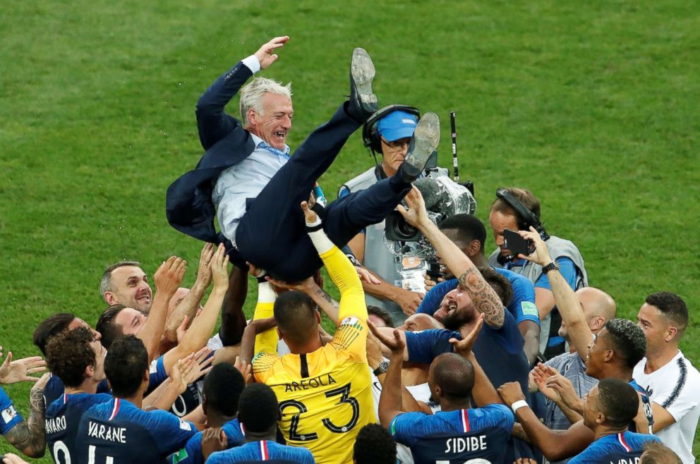 PHOTO: France coach Didier Deschamps is thrown into the air by his players as they celebrate after winning the World Cup on July 15, 2018, at Luzhniki Stadium in Moscow.