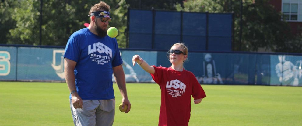 PHOTO: Cody Rice and Kaylynn McSmith attend the kids camp by the Wounded Warrior Amputee Softball Team. The camp connects military veterans on the team with children who have missing limbs.
