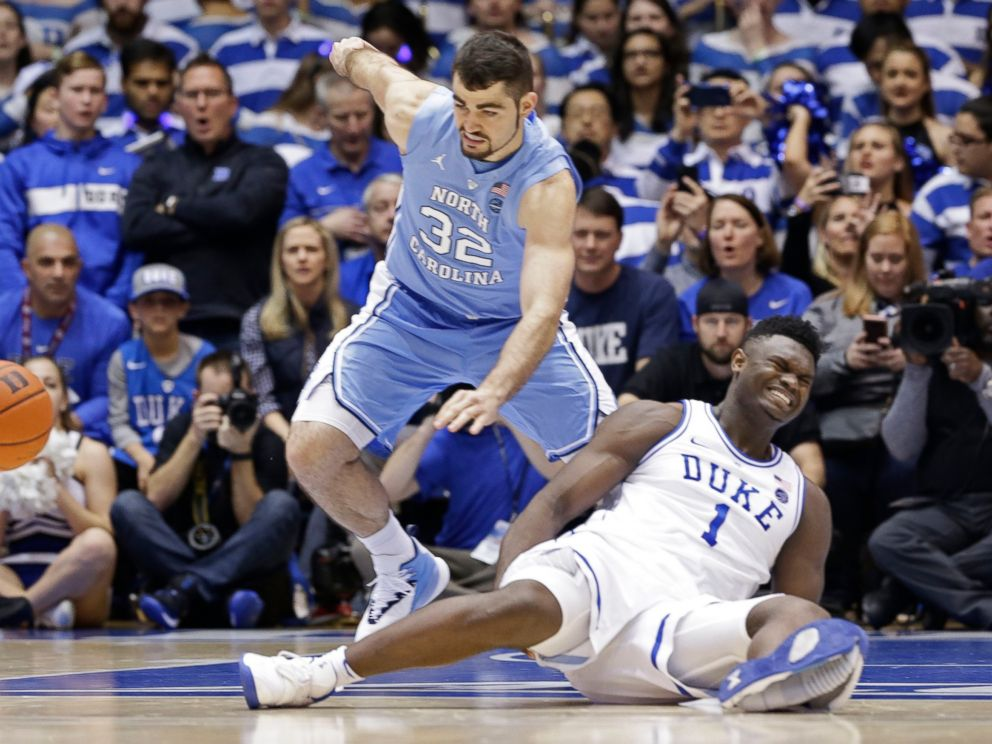PHOTO: Dukes Zion Williamson (1) falls to the floor with an injury while chasing the ball with North Carolinas Luke Maye (32) during the first half of an NCAA college basketball game in Durham, N.C., Wednesday, Feb. 20, 2019.