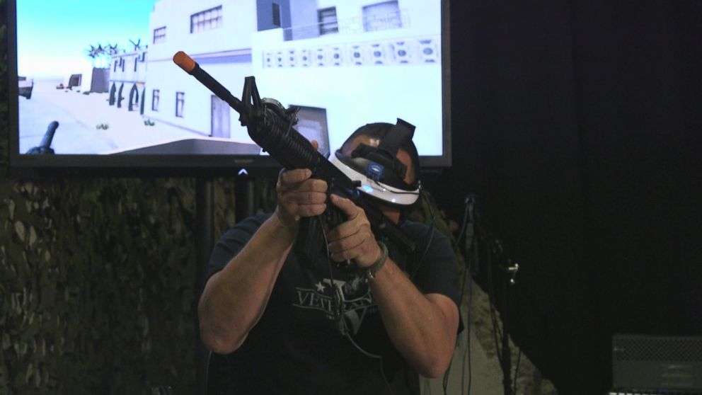 Chris Merkle holds a fake gun while undergoing a virtual reality therapy session that is allowing him to face aspects of his trauma.