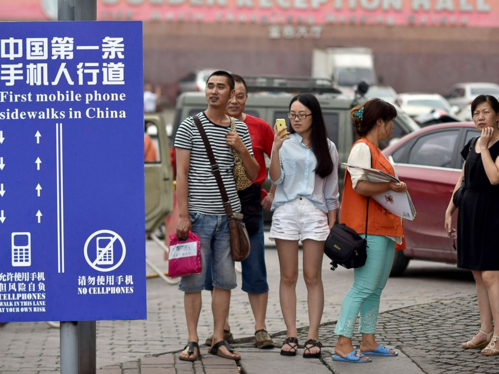 PHOTO: Residents look at a sign with the words Chinas First Cellphone Lane explaining the use of a lane which separates those using their phones as they walk from others in Chinas Chongqing Municipality, Sept. 13, 2014.